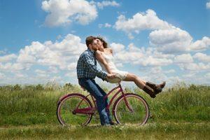 自転車で二人乗りしてデートする男女のカップル