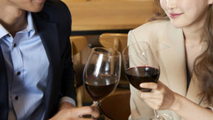 高級レストランで赤ワインで乾杯するカップル