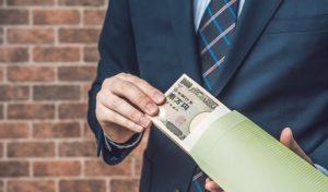 お金(大金)を持つスーツの男性