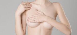 胸を抑える女性(豊胸)